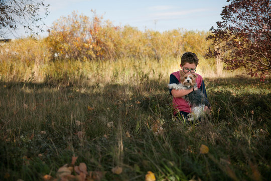 Boy carrying dog while sitting on grassy field at park
