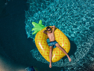 High angle view of shirtless boy with hands behind head relaxing on inflatable ring in swimming pool