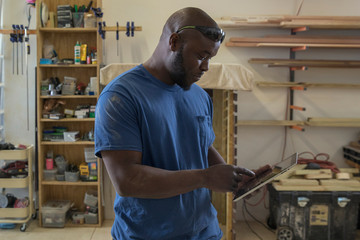 Man using tablet computer while standing in workshop