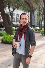 Smiling trendy man with coffee on street
