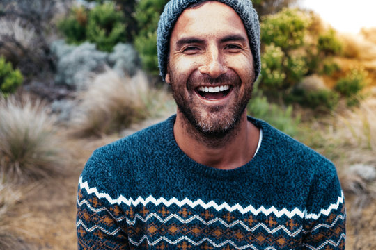 Portrait of cheerful hiker wearing warm clothing on field