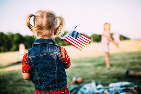 Rear view of girl with small American Flag standing on field at park
