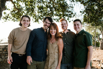 Portrait of happy mother with sons standing at park