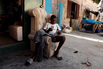 Assndoye sews a pair of trousers in Medina neighbourhood