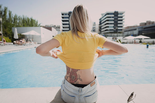 Rear view of tattooed young woman removing yellow t-shirt while sitting on poolside during sunny day