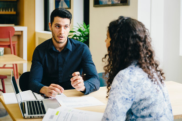 Businessman discussing business plan with female colleague while sitting at desk in office