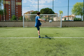 Rear view of boy kicking soccer ball towards net in field