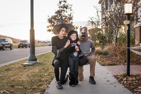 Portrait of siblings in costumes on footpath during Halloween