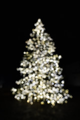 Silhouette of blurry Christmas tree illuminated and decorated with golden, silver and white fairy string lights in dark night creating beautiful bokeh effect with glowing and shiny metallic circles