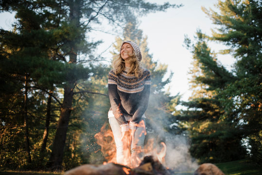 Happy woman standing by campfire against trees in forest