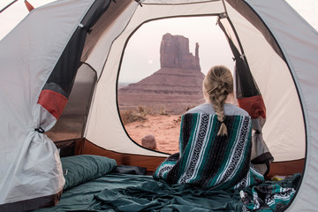 Rear view of woman with scarf sitting in tent at Monument Valley Tribal Park