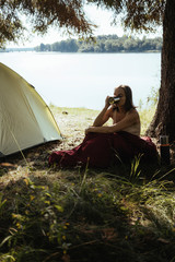 Female hiker in sleeping bag drinking coffee with mug while sitting by tent at forest