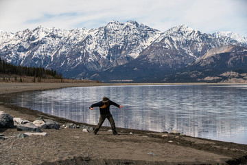Full length of man throwing stone in lake against mountains during winter