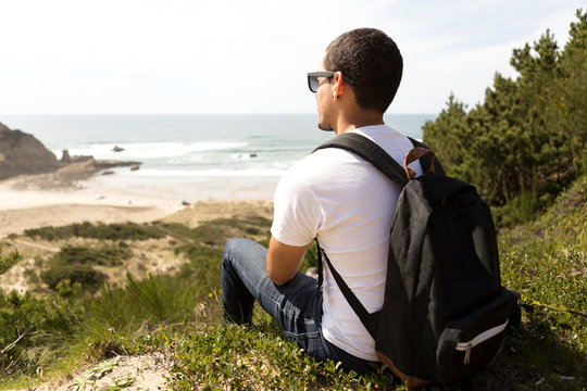 Side view of man with backpack looking at sea while sitting on hill against sky during sunny day