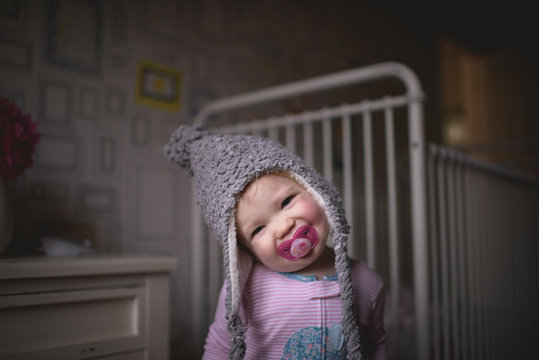 Portrait of girl with pacifier in mouth standing at home
