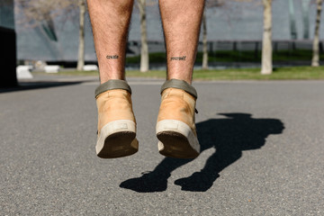 Low section of man with tattoo jumping on road during sunny day