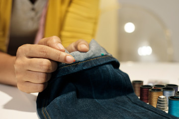 Midsection of female entrepreneur holding jeans on table in office
