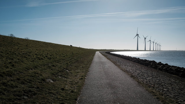 View of empty road leading towards windmills by sea