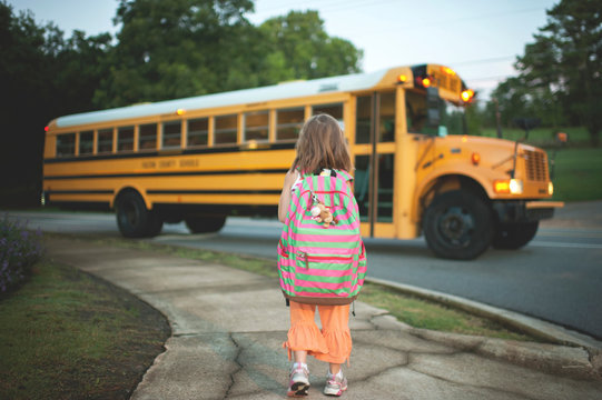 Rear view of girl with backpack waiting for school bus