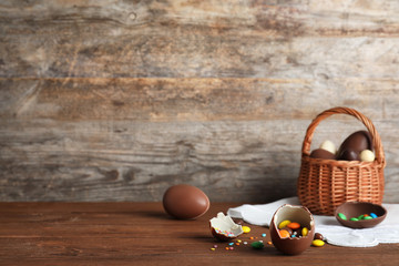 Beautiful composition with chocolate Easter eggs on wooden table. Space for text