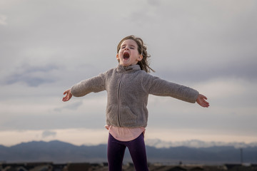 Happy girl with arms outstretched screaming while standing against cloudy sky