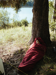 High angle view of female hiker napping in sleeping bag while reclining on tree trunk by lake at forest