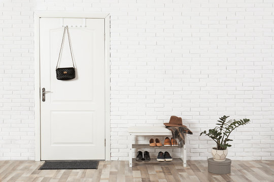 Hall interior with brick wall and white wooden door