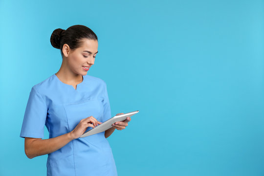 Portrait of young medical assistant with tablet on color background. Space for text