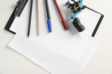 Composition with empty sheet of paper and tattoo machine on white background, top view. Space for text