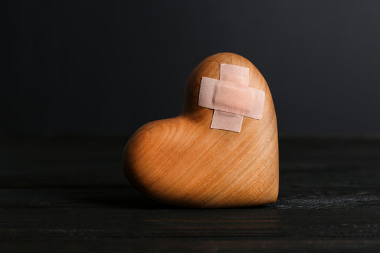 Wooden heart with adhesive plasters in darkness on table