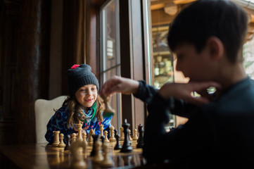 Siblings playing chess by window at home