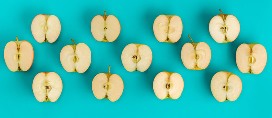 Fruit pattern on blue background. Apple halves geometrical layout. Flat lay, top view. Food background.