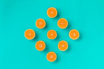 Fruit pattern of fresh mandarin slices on blue background. Flat lay, top view. Pop art design,...
