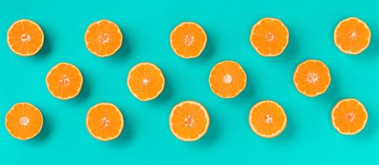 Fruit pattern of fresh mandarin slices on blue background. Flat lay, top view. Pop art design, creative summer concept. Half of citrus in minimal style. Tangerine.