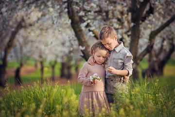 Loving siblings standing amidst plants on field at orchard