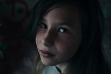 Close-up portrait of girl sitting in darkroom at home
