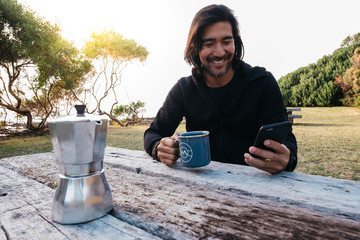 Smiling man having coffee while using smartphone outdoors