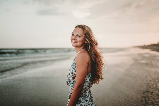 Portrait of happy woman standing at beach against sky during sunset