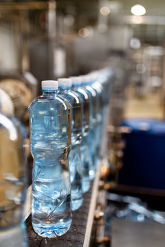 Close-up of water bottles in row at factory