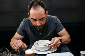 Man eating breakfast while sitting against wall in restaurant