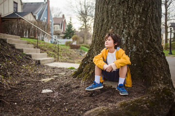 Thoughtful boy looking away while sitting by tree trunk