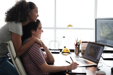 Side view of happy lesbian couple looking at photographs on computers in house