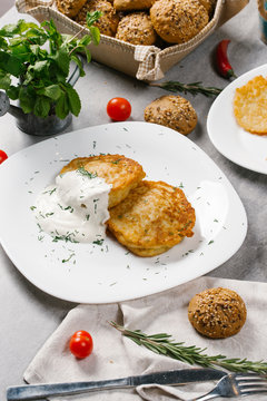 High angle view of potato pancakes with sour cream and dill served in plate on table