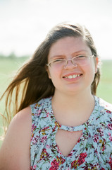 Portrait of overweight teenage girl wearing eyeglasses smiling on field during sunny day