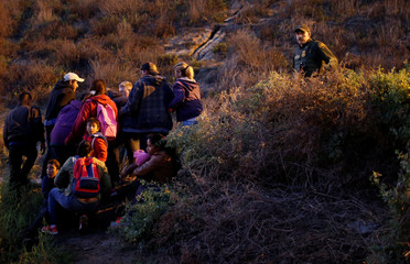 Migrants, part of a caravan of thousands from Central America trying to reach the United States, look at U.S. Customs and Border Protection (CBP) officials in San Diego County, U.S., after crossing illegally from Mexico to the U.S by jumping a border fence