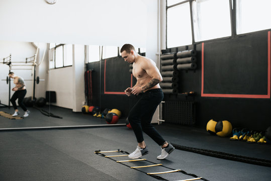 Shirtless young man using agility ladder while warming up in gym