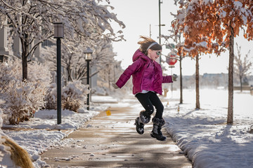 Happy girl jumping on road against sky during winter