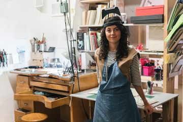 Portrait of confident female artisan standing by table in workshop