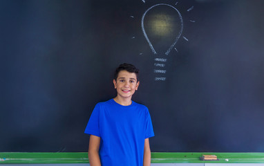 Portrait of schoolboy with light bulb drawing on blackboard standing in classroom