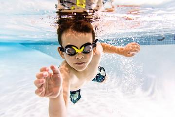 Portrait of shirtless boy swimming underwater in pool